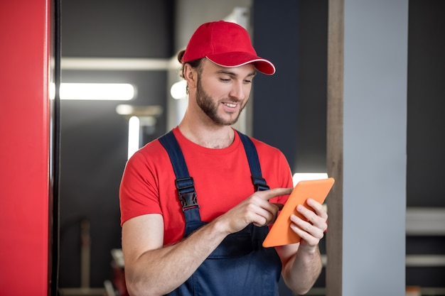 Em formação. homem sorridente interessado com boné vermelho e macacão azul olhando para o tablet tocando o dedo na tela na garagem