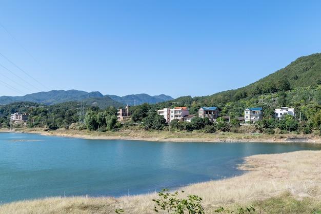 Em frente ao lago está a montanha, o céu é azul e a água do lago é azul