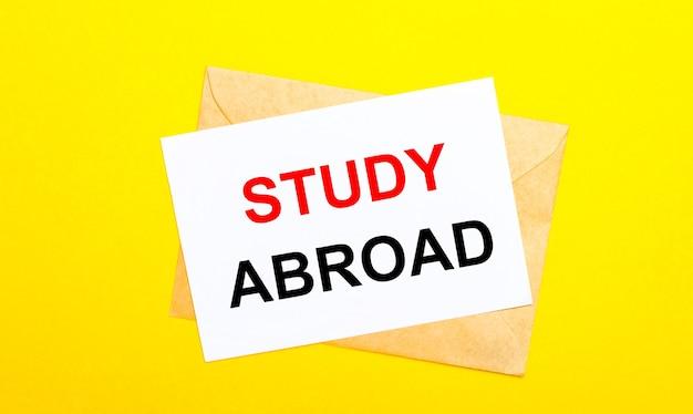 Em fundo amarelo, um envelope e um cartão com o texto estudo no exterior