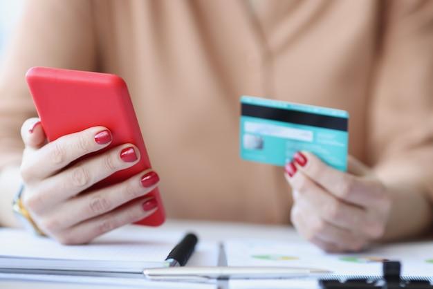 Em mãos femininas, cartão de crédito de plástico e smartphone