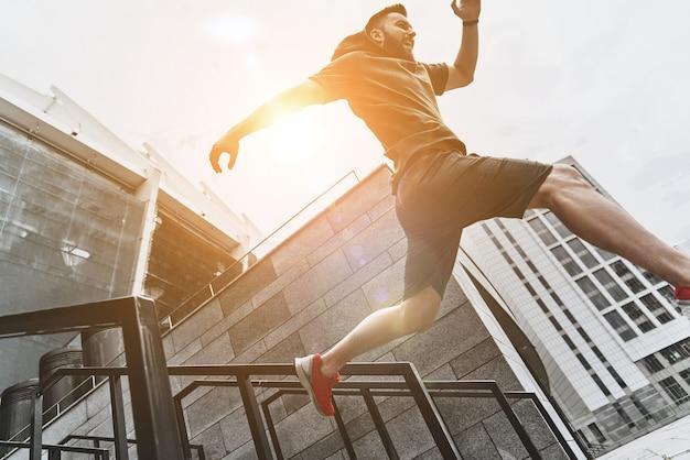 Em movimento. vista de baixo ângulo de um jovem bonito em roupas esportivas pulando
