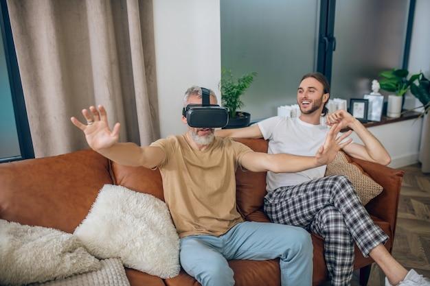 Em óculos de realidade virtual. homem maduro com óculos vr sentado no sofá ao lado de sua parceira