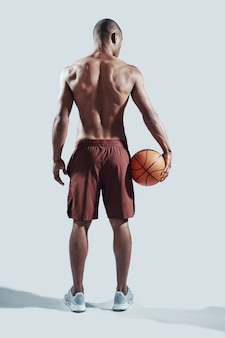 Em ótima forma. retrovisor de corpo inteiro de um jovem africano bonito em roupas esportivas carregando uma bola de basquete em pé contra um fundo cinza