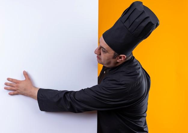 Em pé na vista de perfil, cozinheiro masculino de meia-idade com uniforme de chef, segurando uma parede branca sobre fundo amarelo com espaço de cópia