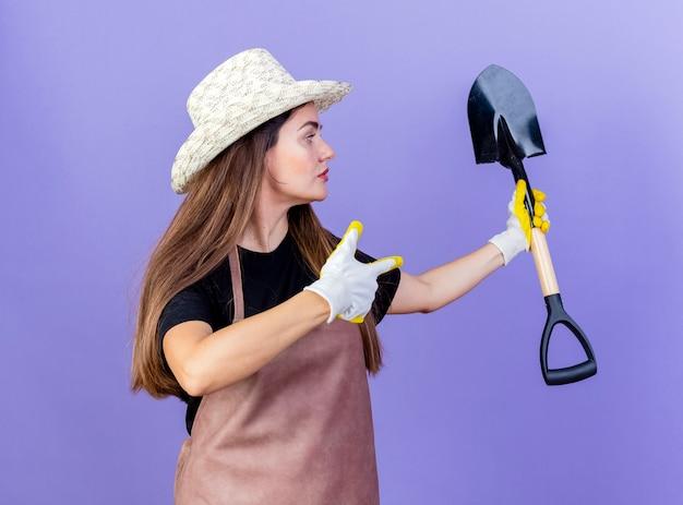 Em pé na vista de perfil, uma linda garota de jardim de uniforme usando chapéu de jardinagem e luvas segurando e aponta para uma pá isolada no azul