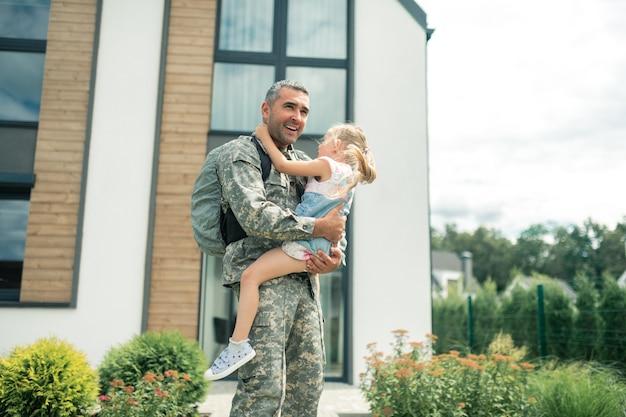 Em pé perto da casa. soldado em uniforme se sentindo incrível em pé perto da casa com a filha