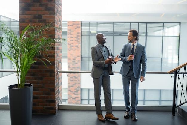 Em pé perto do colega. empresário barbudo, de pele escura, parado perto de seu colega enquanto bebia café