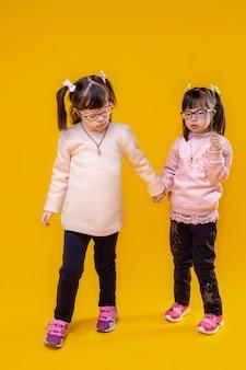 Em pé sob as luzes. garotas bonitas de cabelos escuros com síndrome de down e características incomuns no rosto usando roupas rosa claro