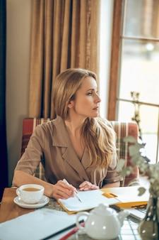 Em pensamentos. mulher loira de cabelos compridos sentada à mesa e parecendo pensativa