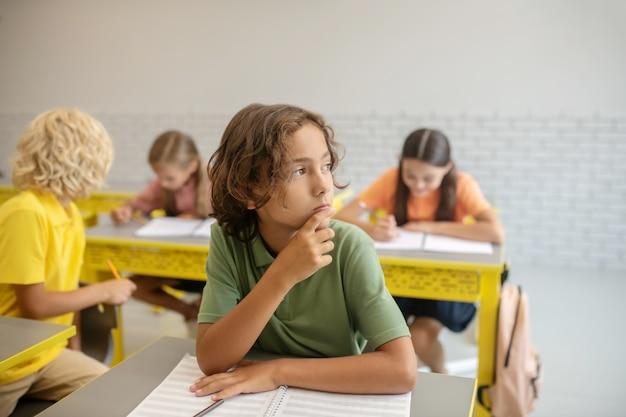 Em pensamentos. um menino sentado na mesa da sala de aula pensando