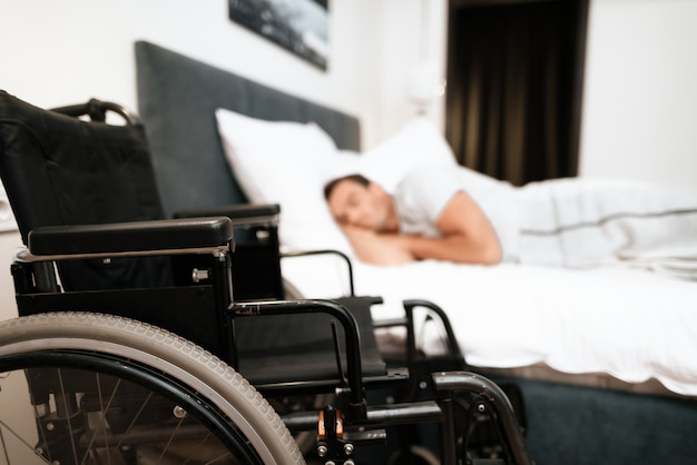 Em primeiro plano está sua cadeira de rodas preta