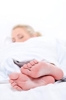 Em primeiro plano, pés limpos de uma mulher bonita dormindo cobrindo o cobertor branco