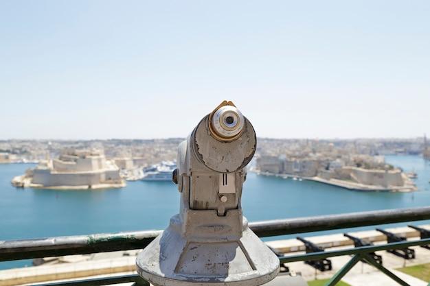 Em primeiro plano, um telescópio operado por moedas, ao fundo, uma vista das cidades de birgu e senglea, malta