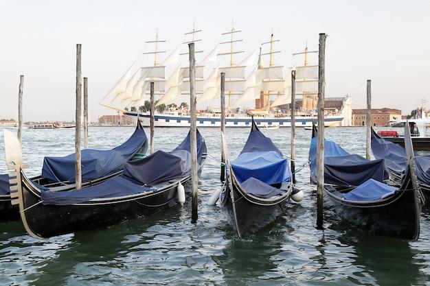 Em primeiro plano, várias gôndolas ao fundo, um enorme veleiro turístico