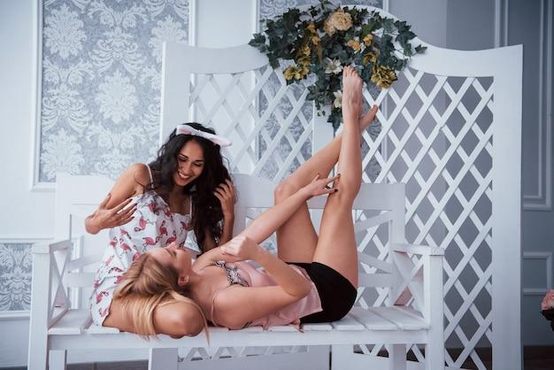 Em processo de conversa. duas garotas na despedida de solteira senta-se e deitado no banco branco