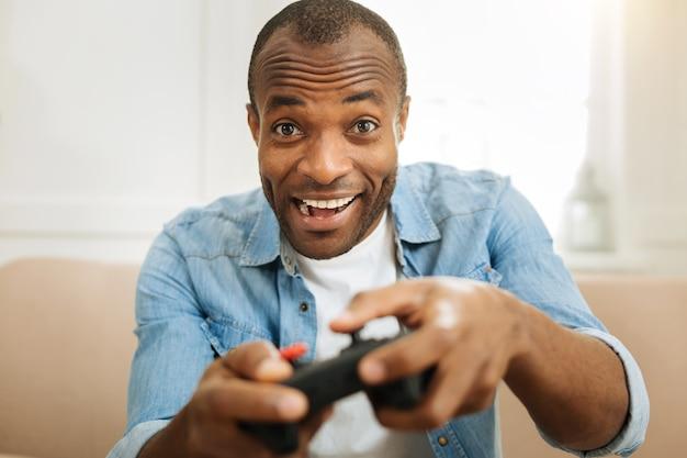 Em repouso. homem afro-americano exuberante e bonito, sorrindo e jogando um jogo com o controle remoto enquanto está sentado no sofá