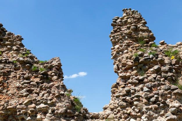 Em ruínas e cobertas de vegetação, ruínas de uma antiga fortaleza, pedras e tijolos, ruínas de estruturas defensivas da idade média
