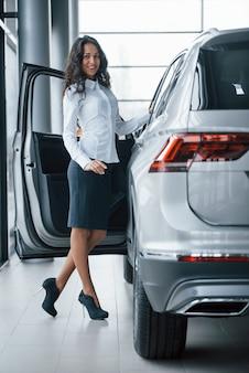 Em saia preta. gerente feminina de cabelos cacheados em pé perto do carro no salão automóvel