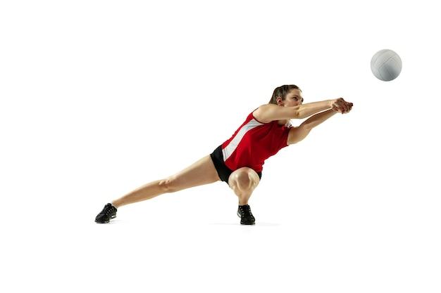Em salto e vôo. jovem jogadora de vôlei isolada na parede branca. mulher em roupas esportivas e tênis, treinando, jogando. conceito de esporte, estilo de vida saudável, movimento e movimento.