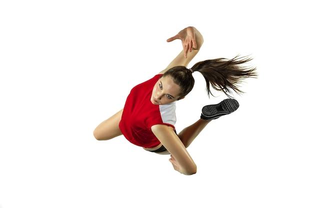 Em salto e vôo. jovem jogadora de voleibol isolada no fundo branco do estúdio. mulher em roupas esportivas e tênis, treinando, jogando. conceito de esporte, estilo de vida saudável, movimento e movimento.