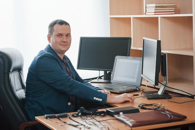 Em seu próprio gabinete. o examinador de polígrafo trabalha no escritório com seu equipamento detector de mentiras