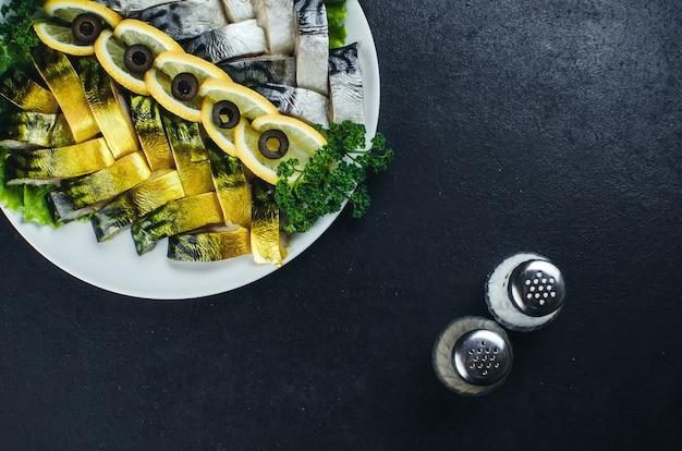 Em tecidos escuros, no prato está um lindo peixe, arenque e salmão decorado com folhagens