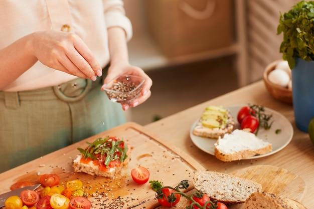Em tons quentes, close-up de uma mulher irreconhecível preparando sanduíches saudáveis de café da manhã com tomate cereja e ervas sobre pão integral