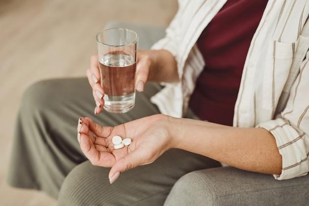 Em tons quentes, close-up de uma mulher irreconhecível segurando comprimidos e um copo de água, medicamento e tratamento de recuperação, espaço de cópia