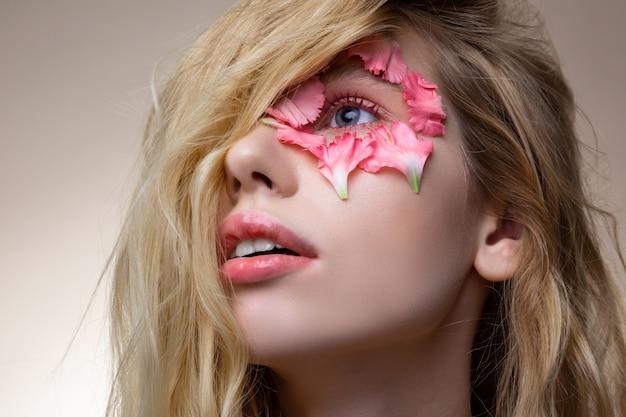 Em torno do olho azul. jovem modelo atraente de cabelos loiros com lábios rosados e pétalas ao redor de olhos azuis