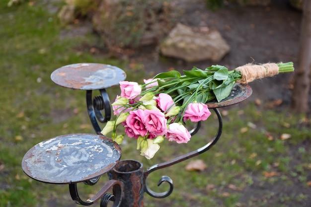 Em um antigo suporte de ferro para vasos de flores, encontra-se um buquê de flores contra um fundo de grama