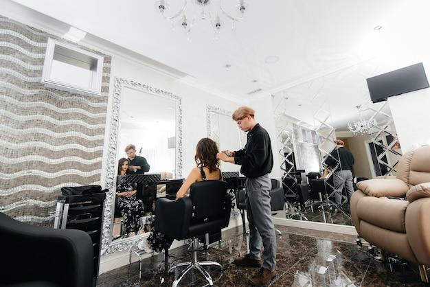 Em um belo e moderno salão de beleza, um estilista profissional faz um corte de cabelo e penteado para uma jovem
