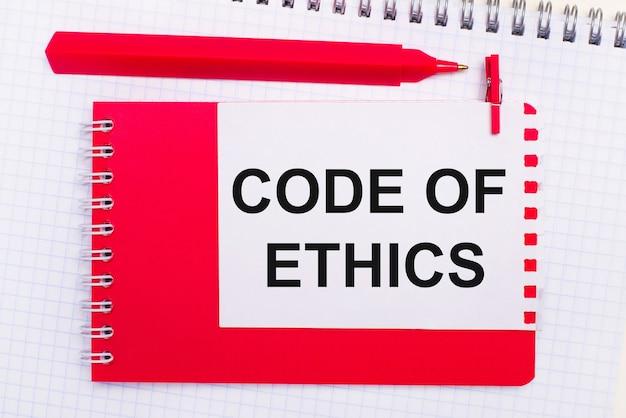 Em um bloco de notas branco, uma caneta vermelha, um bloco de notas vermelho e uma folha de papel branca com o texto código de ética