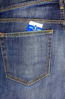 Em um bolso escuro jeans azul inserido bilhete de autocarro