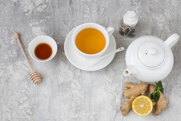 Em um bule de fundo cinza, chá em um copo, limão, hortelã, mel, um frasco para armazenar chá e gengibre