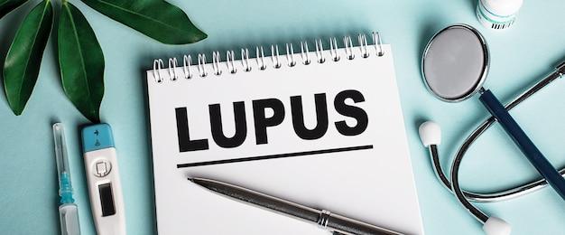 Em um caderno branco em uma parede azul, perto de uma folha de shefflers, um estetoscópio, uma seringa e um termômetro eletrônico, está escrita a palavra lupus. conceito médico