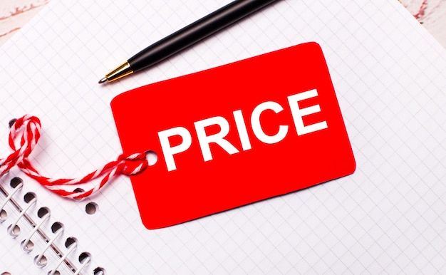 Em um caderno branco, há uma caneta preta e uma etiqueta de preço vermelha em um barbante com o texto preço.