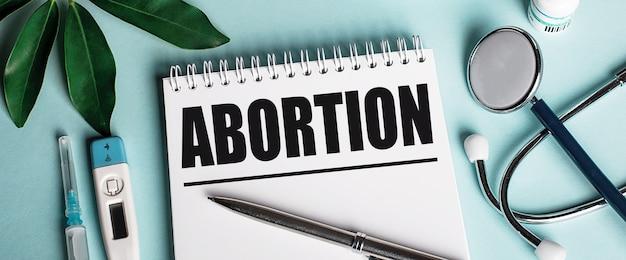 Em um caderno branco sobre fundo azul, próximo a uma folha de shefflers, um estetoscópio, uma seringa e um termômetro eletrônico, está escrita a palavra aborto