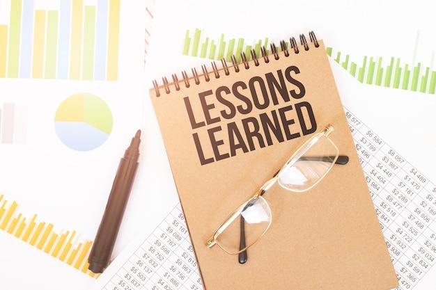 Em um caderno colorido artesanal, há uma inscrição lições aprendidas, ao lado de lápis, óculos, gráficos e diagramas.