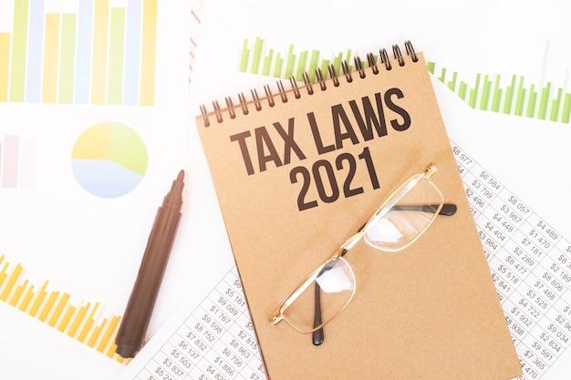 Em um caderno colorido artesanal há uma inscrição tax laws 2021, ao lado de lápis, óculos, gráficos e diagramas.