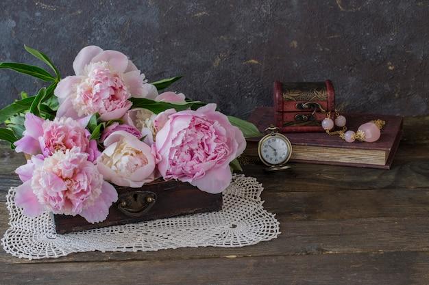 Em um caixão antigo um buquê de peônias rosa, um livro, contas com pedras cor de rosa