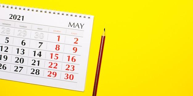Em um calendário de parede amarelo 2021 e um lápis vermelho. vista superior com espaço de cópia.
