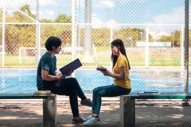 Em um campus, dois alunos estão estudando juntos e um adolescente está sentado em uma cadeira ao lado de uma quadra de esportes com um livro.