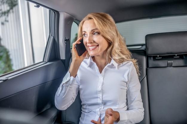 Em um carro. mulher loira bonita sentada em um carro e falando ao telefone