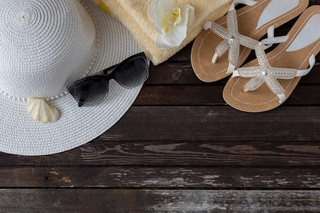 Em um chapéu de mesa de madeira, flip-flops, óculos de sol, toalha, casca e orquídea