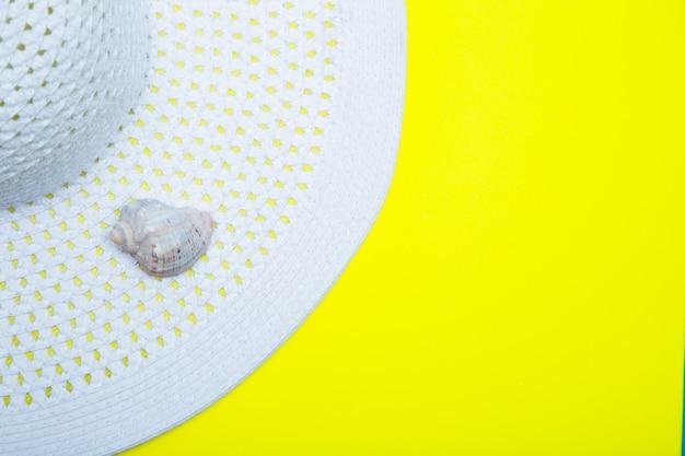 Em um chapéu de sol branco com aba larga, há uma concha sobre um fundo amarelo com um lugar para texto. foto de alta qualidade
