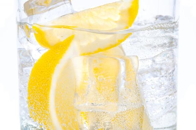 Em um copo com cubos de gelo derretendo fatias de um limão suculento.