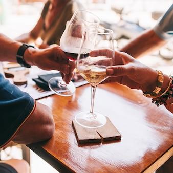 Em um dia de sol, as pessoas comem queijo e bebem vinho no restaurante do terraço.