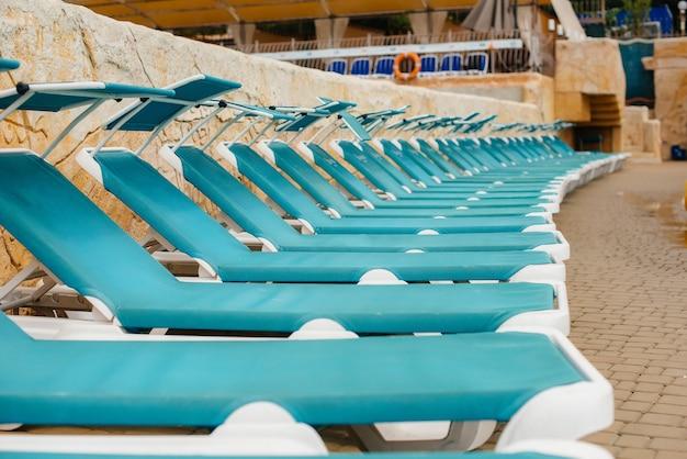 Em um dia ensolarado, há várias novas e lindas espreguiçadeiras azuis perto da piscina do hotel. boas férias de férias. férias de verão e turismo.