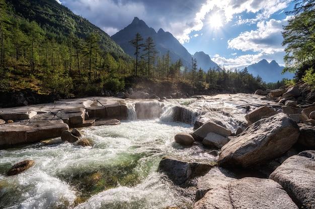 Em um dia quente de verão e ensolarado, um rio de montanha corre sobre as pedras lisas lavadas ao longo dos anos