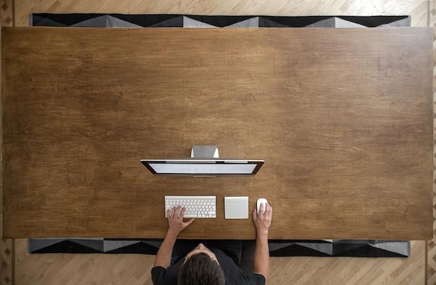 Em um espaço de coworking, um homem sentado em uma mesa de madeira vazia trabalha em um laptop, desenvolve software.